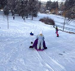 Family sledding adventure in Drake Park.
