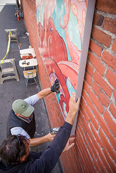 "Crews install Taylor Rose's painting, ""Tangled,"" in Tin Pan Alley."