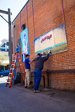 "Crews install ""Voyage"" by Caroline Cornell and ""Klondike Kate"" by Sheila Dunn in the alley beside Toomies."