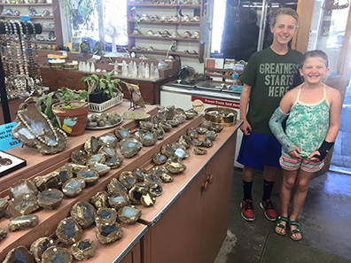 Cedar (age 13) and Violet (age 9) pose in front of a display of thundereggs in the gift shop at Richardson's Rock Ranch before heading out for a morning of rockhounding.