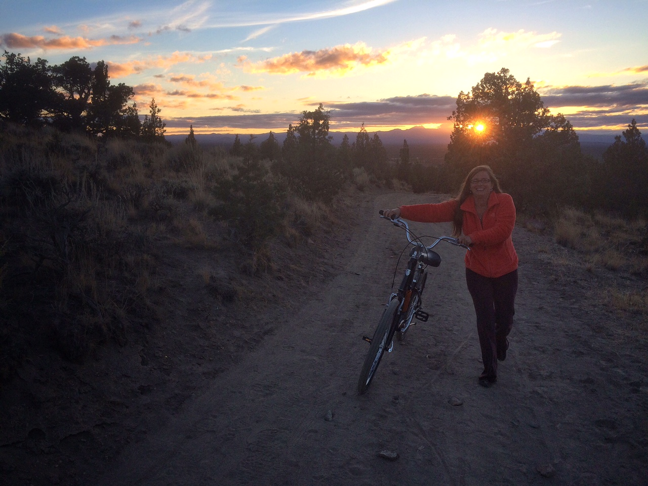 Tawna walks her bike (hey, it was steep!) up to Spirit Rock for sunset.