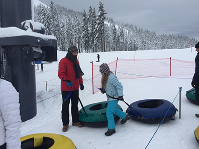 Craig and Violet wait in line to be hauled to the top of the Snowblast Tubing Park at Mt. Bachelor.
