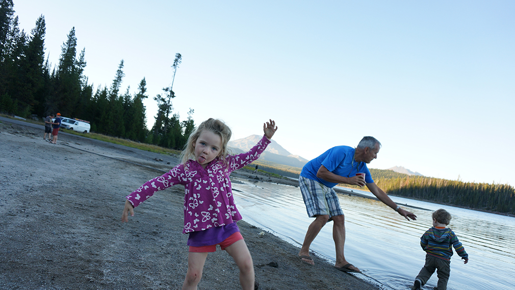Kevney's kids frolic with their grandpa on the shore of Elk Lake.